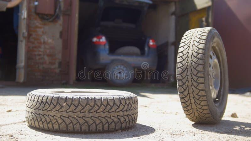 Den unga mannen kastar bort hjulet från hans bilstam royaltyfria foton