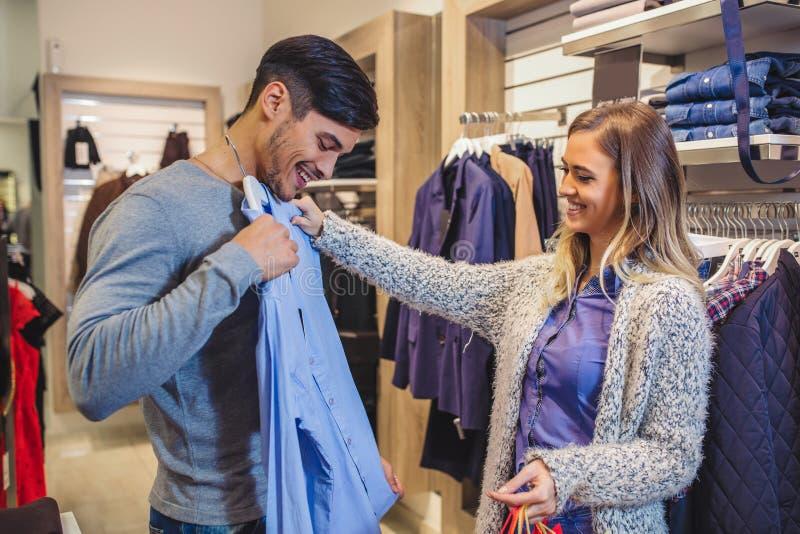 Den unga mannen konsulterar med flickvännen, medan välja en skjorta fotografering för bildbyråer