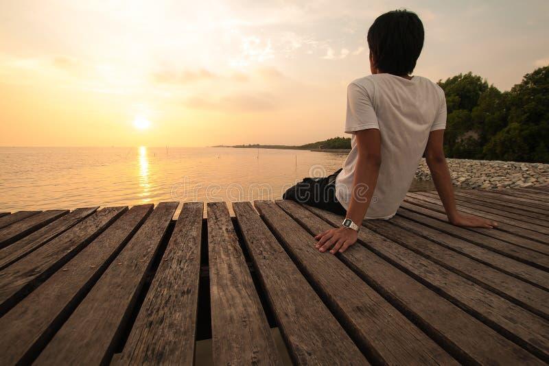 Den unga mannen kopplar av att placera på pirblickar framåtriktat med solnedgång royaltyfri bild