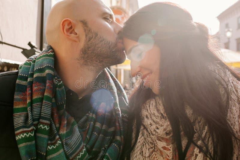 Den unga mannen kysser hans flickvän i staden arkivfoton