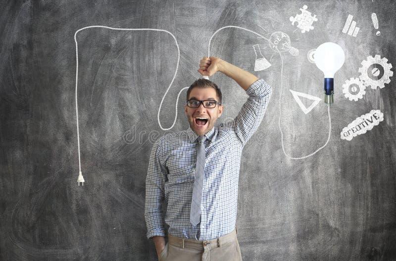 Den unga mannen ler och rymmer en ljus ljus kula arkivfoton