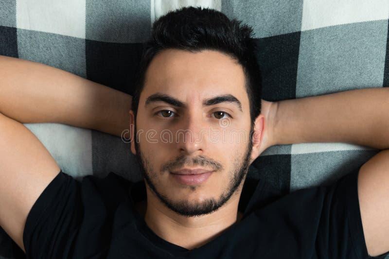 Den unga mannen ligger i säng royaltyfri foto