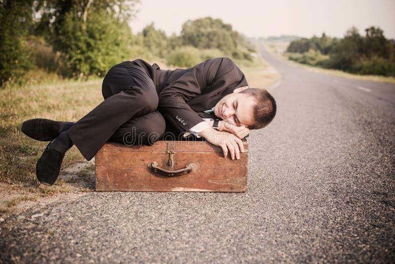Den unga mannen ligger på den gamla resväskan royaltyfri bild