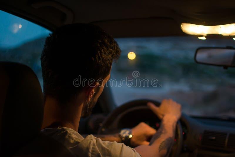 Den unga mannen med örhängen kör en bil på natten arkivbild