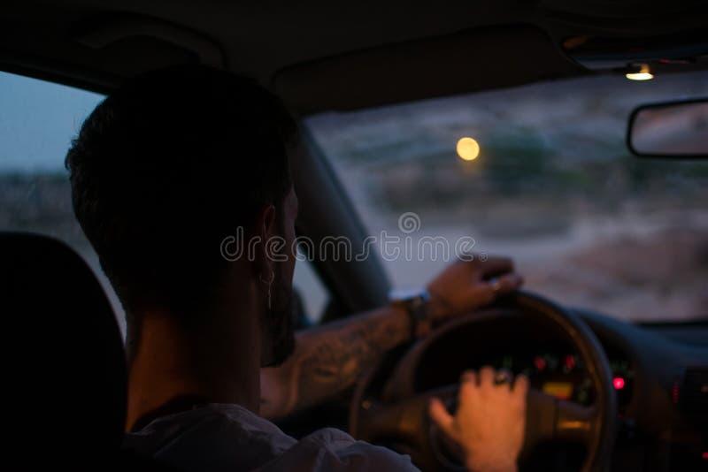 Den unga mannen med örhängen kör en bil på natten arkivbilder