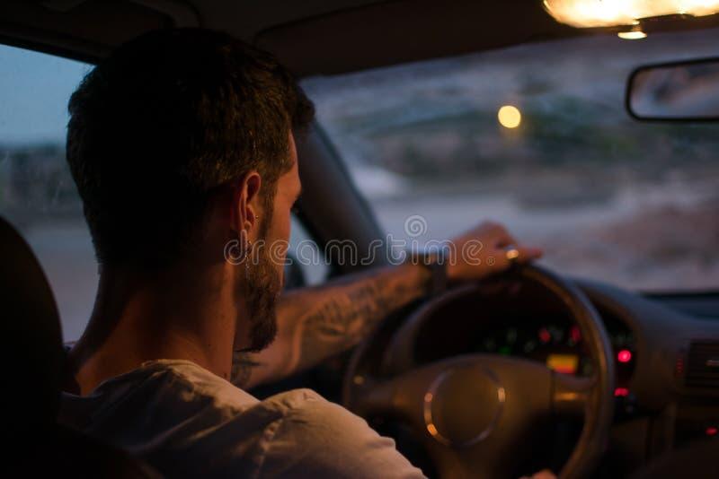 Den unga mannen med örhängen kör en bil på natten royaltyfri fotografi