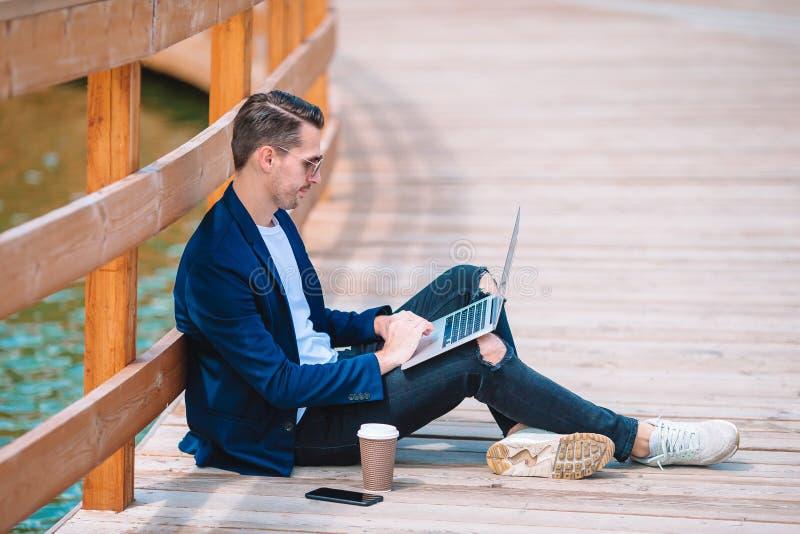 Den unga mannen med bärbar datorarbete i parkerar utomhus arkivfoton