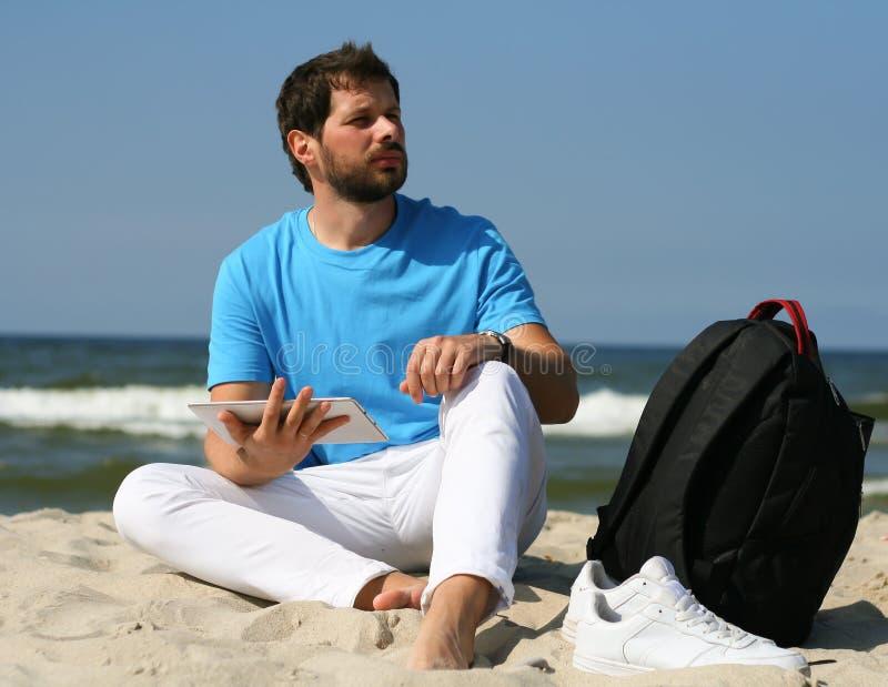 Den unga mannen med bärbara datorn och ryggsäcken under stranden semestrar arkivbild
