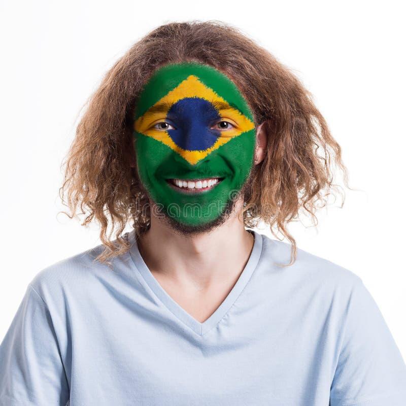 Den unga mannen med den Brasilien flaggan målade på hans framsida royaltyfria foton