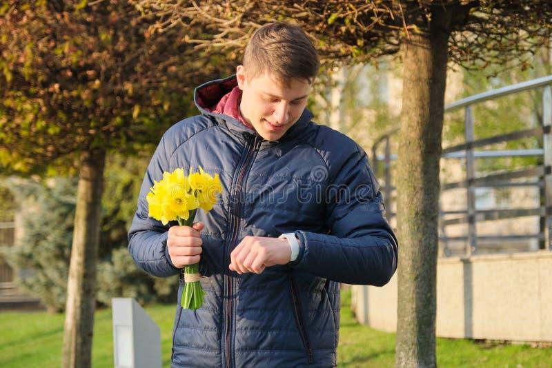 Den unga mannen med buketten av vårblommor ser armbandsuret, stads- bakgrund, mannen som väntar hans flickvän royaltyfri bild