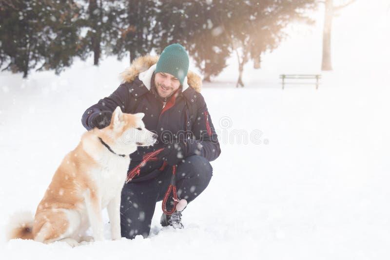 Den unga mannen med det akita hundhusdjuret parkerar in på snöig dag fotografering för bildbyråer