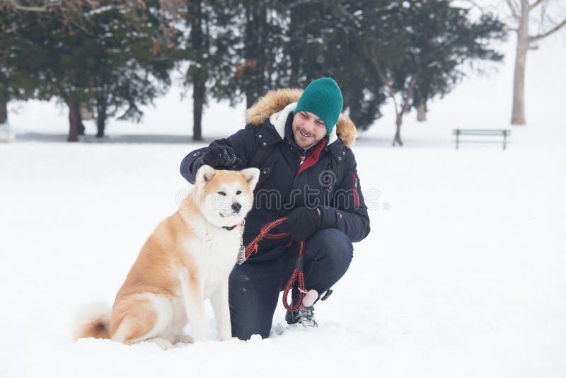 Den unga mannen med det akita hundhusdjuret parkerar in på snöig dag Vinterconcep arkivfoto