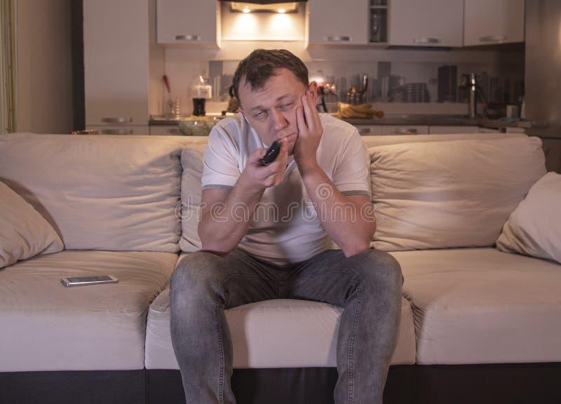 Den unga mannen med en uttråkad blick i aftonen sitter hemma på soffan med en fjärrkontroll- och hålla ögonen påTV royaltyfria foton