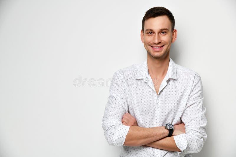 Den unga mannen med ett brett snällt leende står på den vita väggen med armar som korsas nära utrymme för fri text royaltyfria bilder