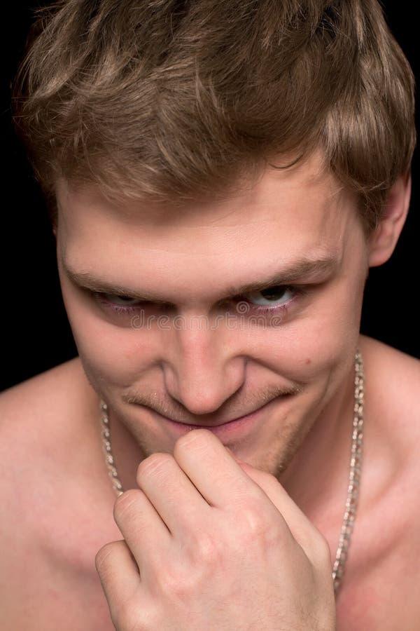 Den unga mannen med ett ondsint grinar fotografering för bildbyråer