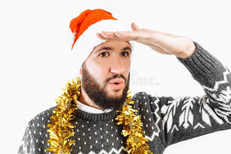 Den unga mannen med ett skägg, en man i en Santa Claus hatt, ser in i avståndet, det kommande nya året arkivfoto
