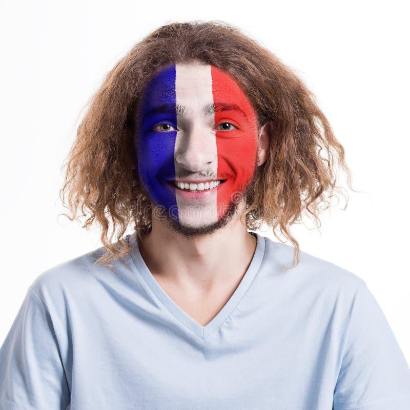 Den unga mannen med den Frankrike flaggan målade på hans framsida royaltyfri fotografi