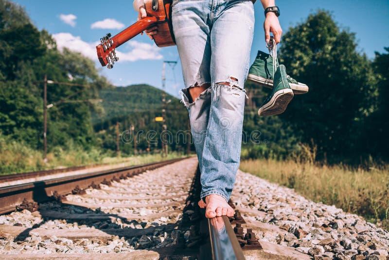 Den unga mannen med gitarren går på den järnväg vägen, ben för slut avbildar upp royaltyfria bilder