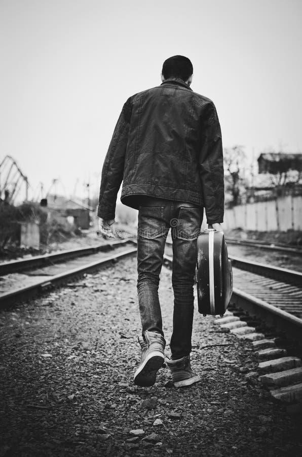 Den unga mannen med gitarrfallet i hand går bort. Bakre sikt som är svartvit royaltyfria foton