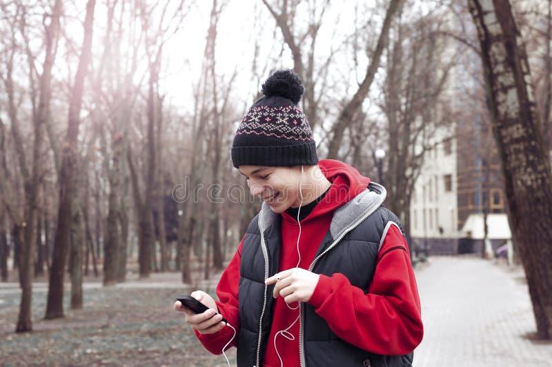 Den unga mannen med mobiltelefonen i stad parkerar royaltyfria bilder