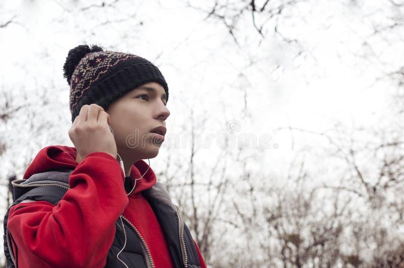 Den unga mannen med mobiltelefonen i stad parkerar arkivfoton