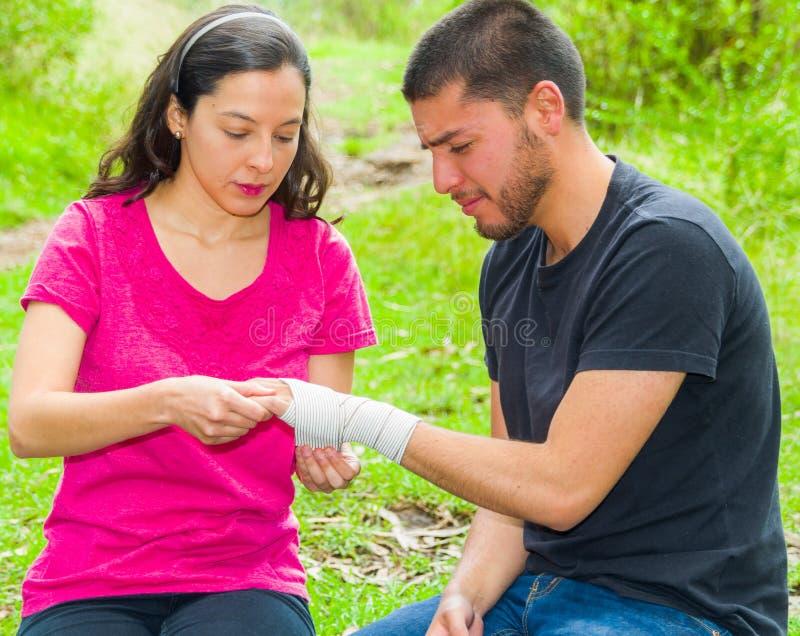 Den unga mannen med sårat handledsammanträde och att få förbinder kompressionssjalen från kvinnlign, utomhus miljö fotografering för bildbyråer
