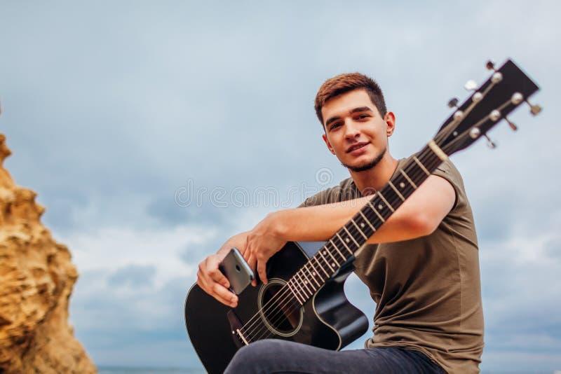 Den unga mannen med sammanträde för akustisk gitarr på stranden som omges med, vaggar på regnig dag genom att använda smartphonen arkivfoton