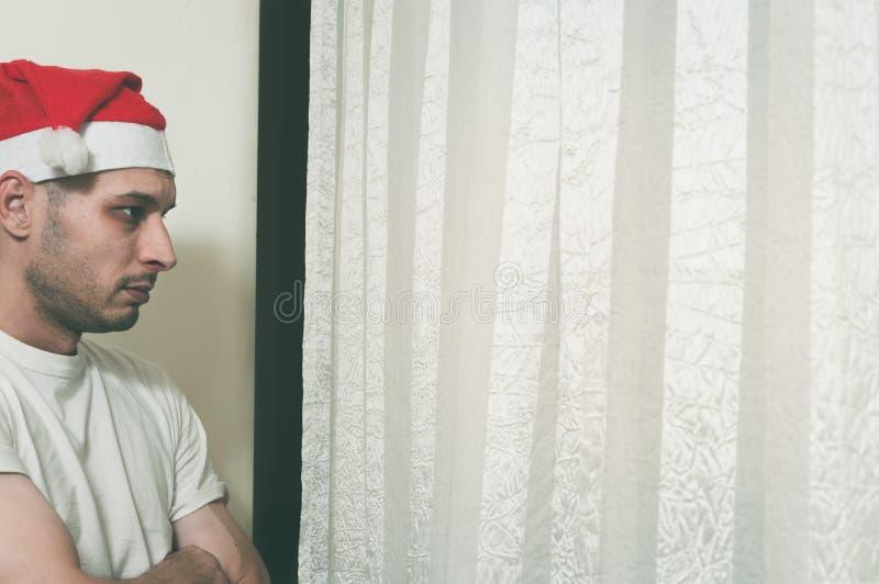 Den unga mannen med den Santa Claus hatten som ser till och med fönstret som känner sig ensamt och ledset för nytt år och jul, se arkivbild