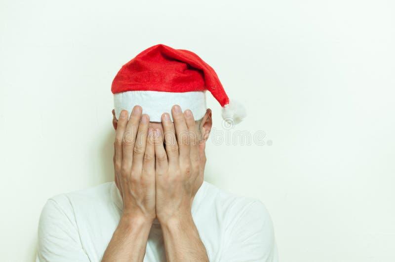 Den unga mannen med den Santa Claus hatträkningen hans framsida med hans händer som känner sig ensamma och ledsna för nytt år och fotografering för bildbyråer