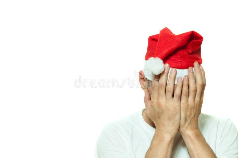 Den unga mannen med den Santa Claus hatträkningen hans framsida med hans händer som känner sig ensamma och ledsna för nytt år och royaltyfri foto