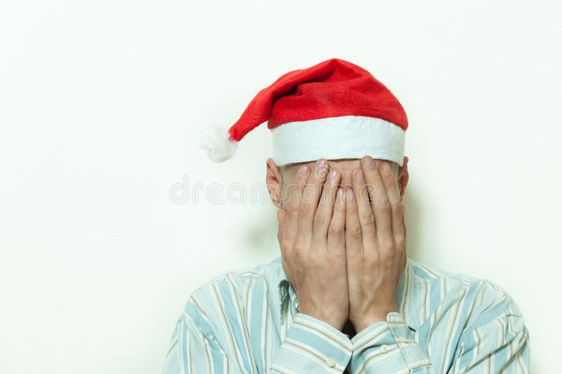 Den unga mannen med den Santa Claus hatträkningen hans framsida med hans händer som känner sig ensamma och ledsna för nytt år och arkivbild