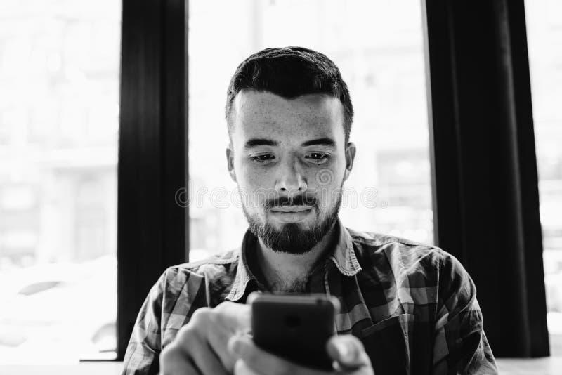 Den unga mannen med skägget är upptagen och genom att använda hans smartphone arkivbild