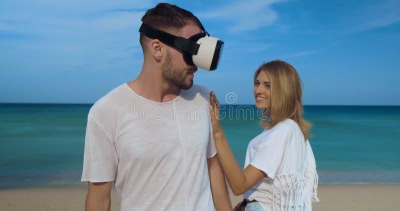 Den unga mannen med virtuell verklighetexponeringsglas som möter den härliga kvinnan, daterar på stranden royaltyfria foton