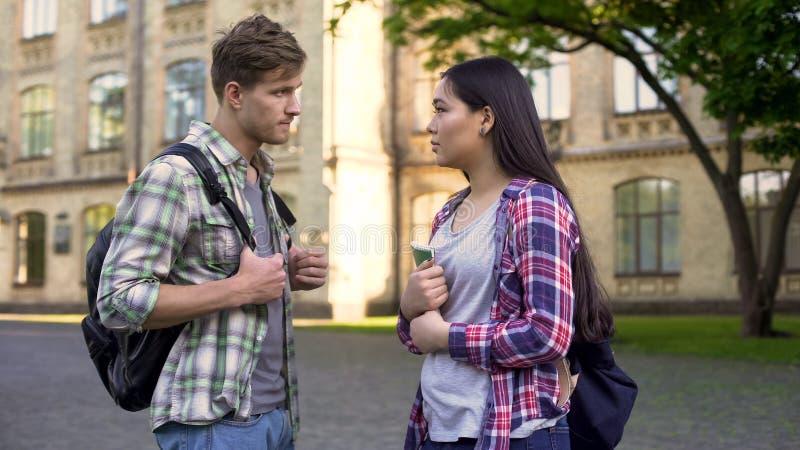 Den unga mannen meddelar med geekflickastudenten, frågar för hjälp i examenförberedelse royaltyfria foton