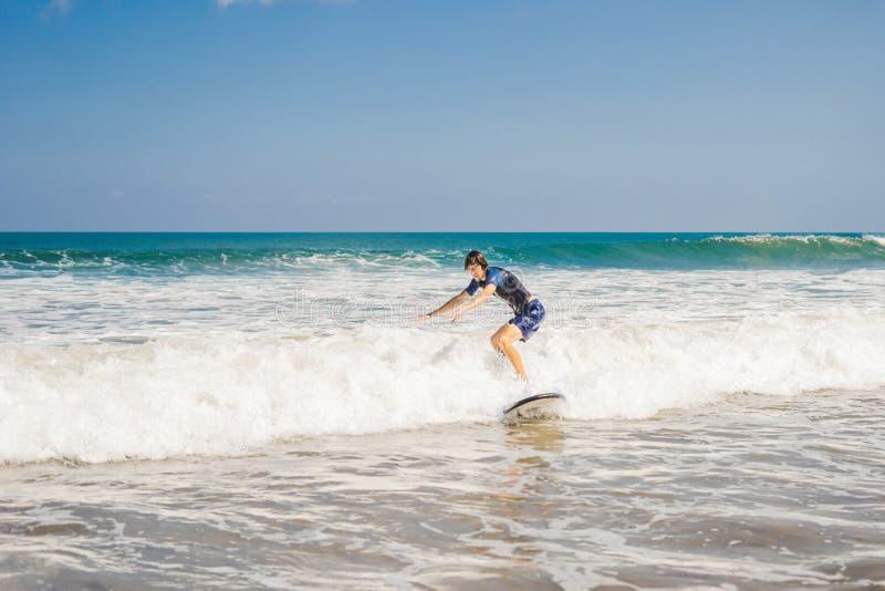 Den unga mannen, nybörjaresurfare lär att surfa på ett havsskum på bet royaltyfri fotografi