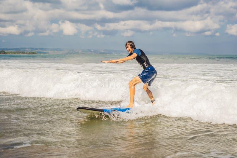 Den unga mannen, nybörjaresurfare lär att surfa på ett havsskum på bet arkivbilder