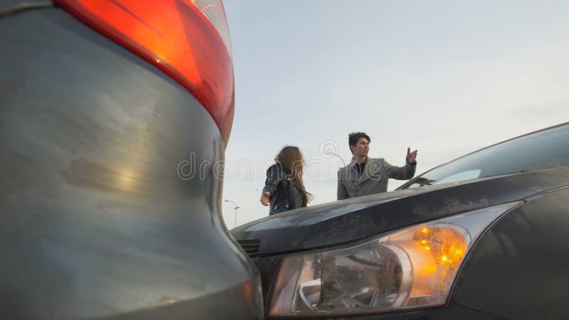 Den unga mannen och kvinnan argumenterar på grund av bilolyckan royaltyfri fotografi