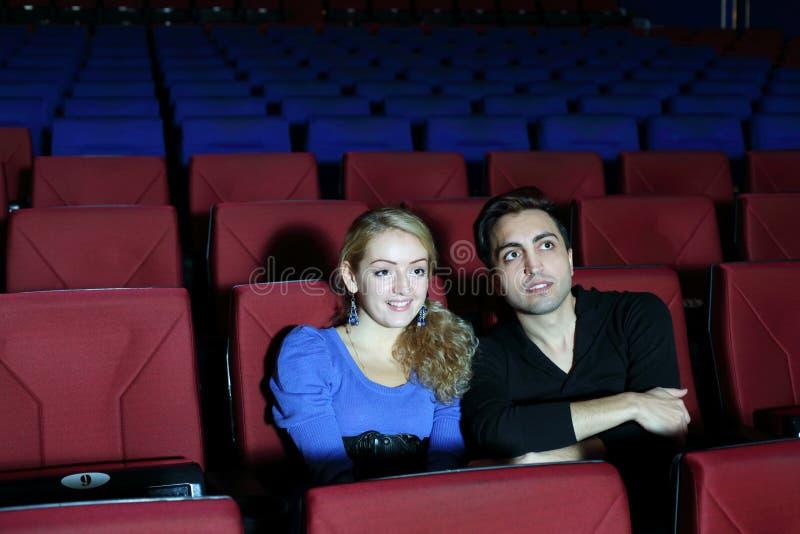 Den unga mannen och kvinnan håller ögonen på film i filmbiograf arkivfoton