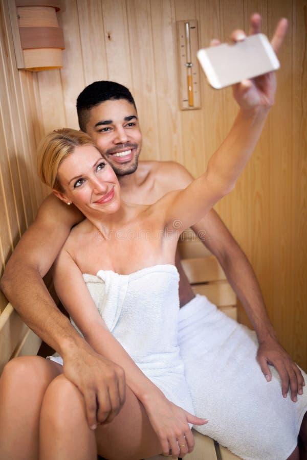 Den unga mannen och kvinnan kopplar av i bastu- och danandesjälven, med mo fotografering för bildbyråer