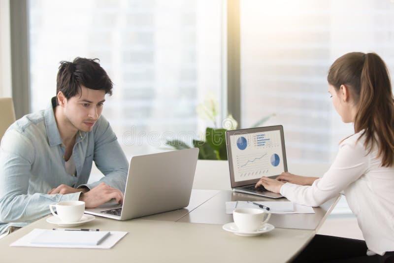 Den unga mannen och kvinnan som arbetar på kontoret, bordlägger genom att använda bärbara datorer royaltyfri bild