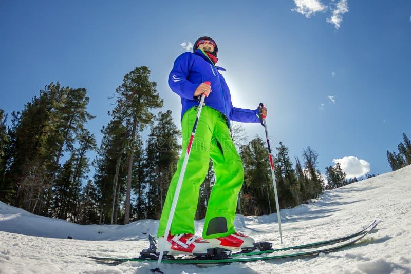 Den unga mannen på alpin skidåkning står på ett snöig spår mot himlen royaltyfri bild