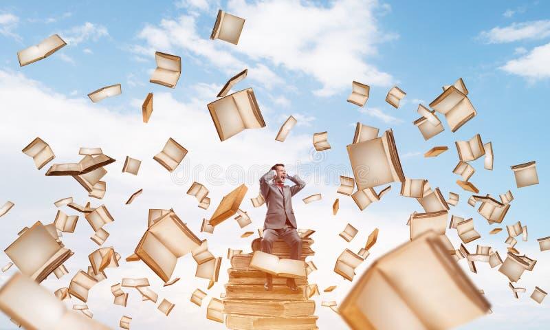 Den unga mannen på högen av böcker önskar inte att höra något arkivbild