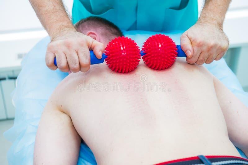 Den unga mannen p? sjukgymnastiken som mottar bollmassage fr?n kiropraktor f?r terapeut A, behandlar patientens thorakala rygg i  royaltyfri fotografi