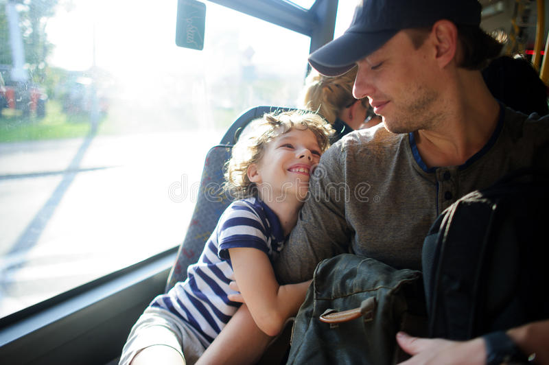 Den unga mannen passerar bussen samman med sonen arkivbilder