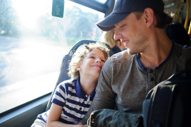 Den unga mannen passerar bussen samman med sonen royaltyfri foto