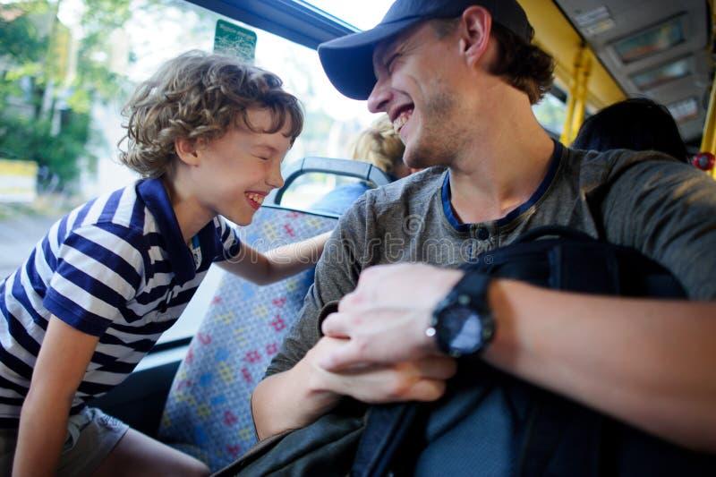 Den unga mannen passerar bussen samman med sonen royaltyfri fotografi