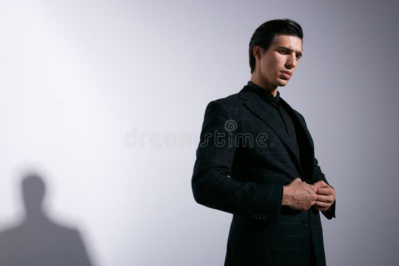 Den unga mannen poserar i studio med attitudine och att se kameran som justerar hans dräkt som isoleras på vit bakgrund fotografering för bildbyråer