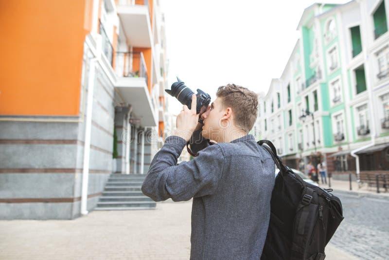 Den unga mannen promenerar gatorna av en gammal härlig stad med en kamera i hans hand- och fotografiarkitektur arkivfoton