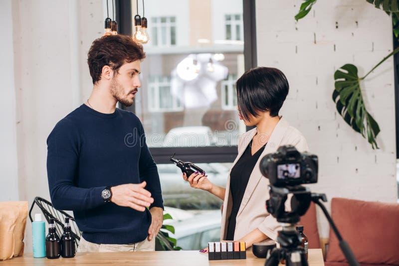 Den unga mannen råder en ny lotion till en modeflicka royaltyfri bild