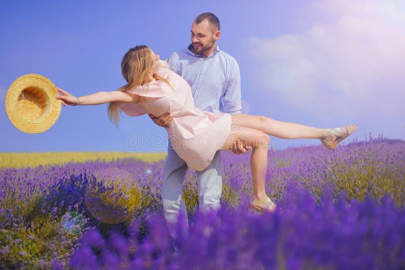 Den unga mannen rymmer kvinnan i lavendelfältet, förälskat gå för gulliga barnpar i ett fält av lavendelblommor Flickan lyfter up fotografering för bildbyråer